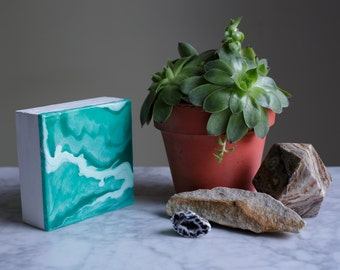 """Fluid artwork named """"Malachite Green II"""", in green and white on 4""""x4""""x1.5"""" wood panel by Kirsten Gilmore"""