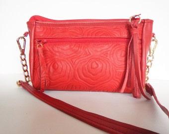 Crossbody bag, or shoulder bag in red leather. Red leather sling bag with embossed modern rose design.