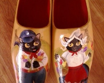 Hand painted clogs with black cats in traditional dutch costumes and scenery.