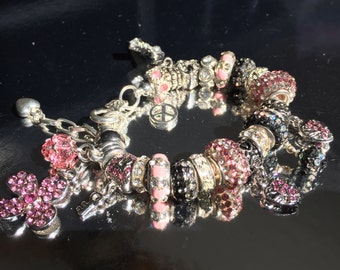 Pink and black beaded crystal bracelet with charms.