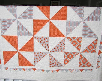 Orange, grey, and white modern gender neutral, pinwheel quilt for baby boy or girl.