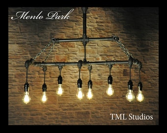 The Menlo Park industrial chandelier light fixture featuring vintage Edison pendant style filament bulbs, black plumbing gas pipe and chains