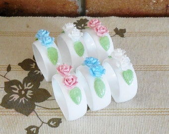 6 white porcelain napkin rings with blue, pink and white rose detail perfect condition
