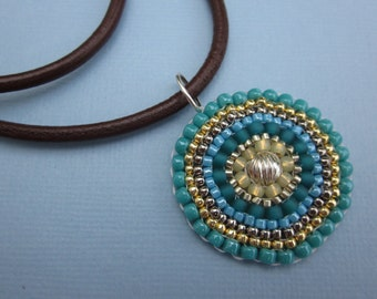 turquoise and gold seed bead medallion necklace on brown leather cord