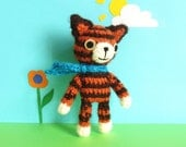 Crochet tiger in orange and brown with cute face and blue scarf