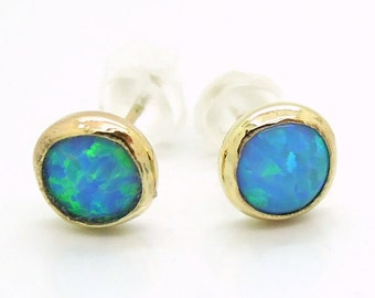 Round gold stud earrings with opal, wrapped design
