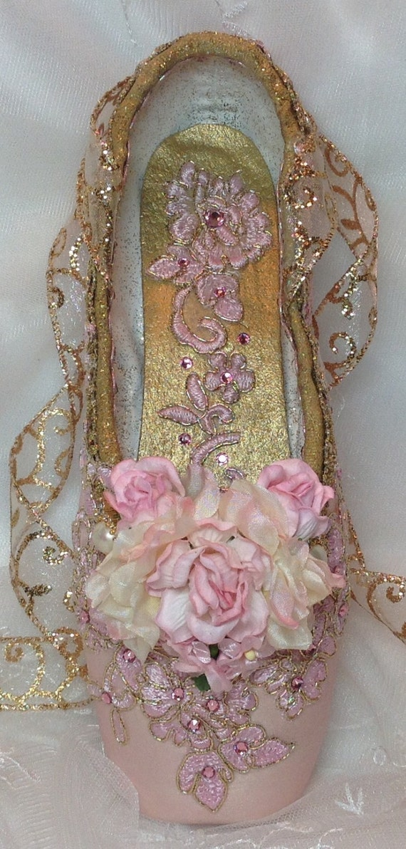 I pair of pink and gold decorated pointe shoe for Ballet shoes decoration
