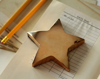 Vintage brass star paperweight with fabric backing  / star paper weight