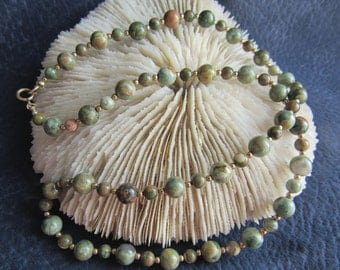 Necklace gemstone ryolite, 4mm and 6mm rounds, 18 in with 12k goldfilled accent beads and clasp.  Shades of olive creams and some brown.