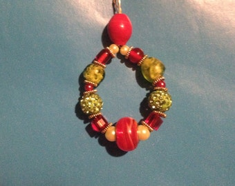 Red, green, and gold sparkle beaded pendant on link chain.