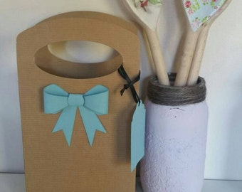 Brown card gift bag with blue 3D bow and tag.