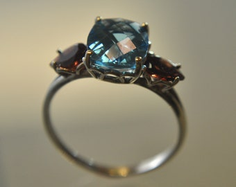 14kt White gold Ring with Swiss Blue Topaz and Mozambique Garnets in a Size 8