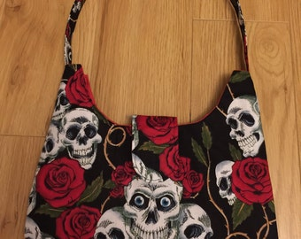 Larger top handled bag, black featuring skulls and red roses