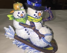Ceramic snowmen on sled sparkled and glittered as well as hand painted