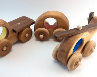 set of 3 wooden toy vehicles, truck, helicopter, smart car, all natural with a hint of colour. By Bruce Hay