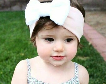 Light pink headwrap with white bow.