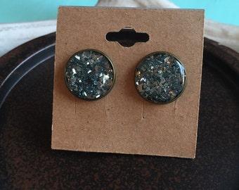 Light blue glass glitter stud earrings sealed with resin.