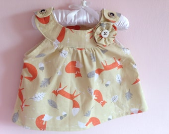 Handmade, babies top, beige with orange foxes and rosette detail