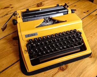 Typewriter Erika 100-106, orange. Working vintage portable typewriter. Made in Easy Germany 1980.