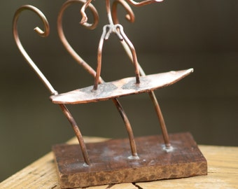 Copper Art Figurine of a surfer riding a wave.
