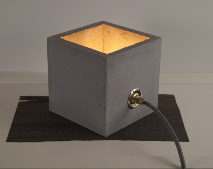 be the light little concrete lamp with brass and gold