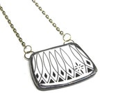Broken plate necklace . black and white diamond geometric pattern . saucer rim . 1960s