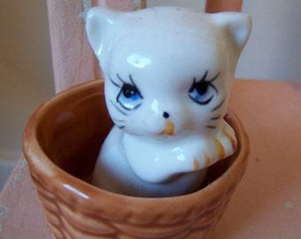 tiny kitten in a basket figurine