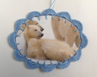Crochet Christmas Ornament Card made from recycled card. Adorable polar bear relaxing in the snow. Blue crochet edge.
