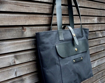 Waxed canvas tote bag with large outside pocket and leather handles