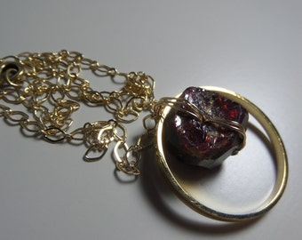 Rough cut garnet with brass necklace.