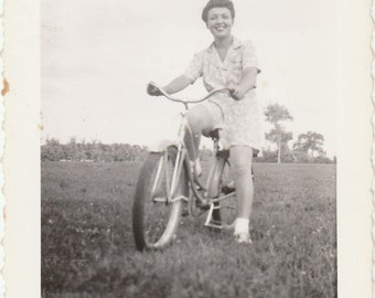 1940's Pretty young woman riding bicycle in field vintage photo