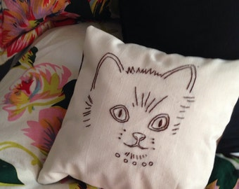 Decorative cat face embroidered cream colored pillow brown plaid backing