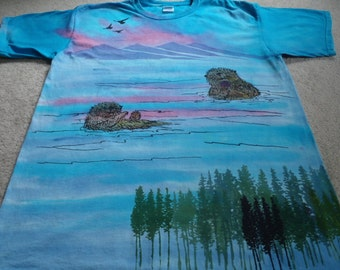 Sea otters playing catch with a sea urchin, birds flying above the mountains, fir trees,  man's XL screen printed and dyed t-shirt