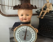 Vintage doll head assemblage using vintage items including a scale and birdcage