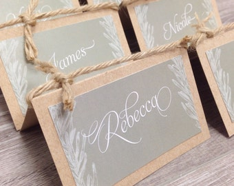 Folded rosemary escort cards customized with guest name and optional table number. Colour customizable. Kraft, twine and rosemary design.