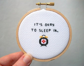 "It's okay to sleep in completed cross stitch -- tiny alarm clock, finished cross stitch from ""It's Okay"" series"