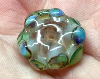 Lampwork focal bead with a clear base and organic textured dots of greens and browns
