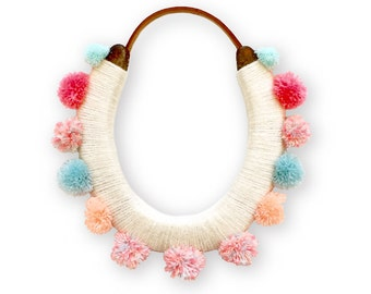 lucky yarn wrapped horseshoe with pastel pom poms