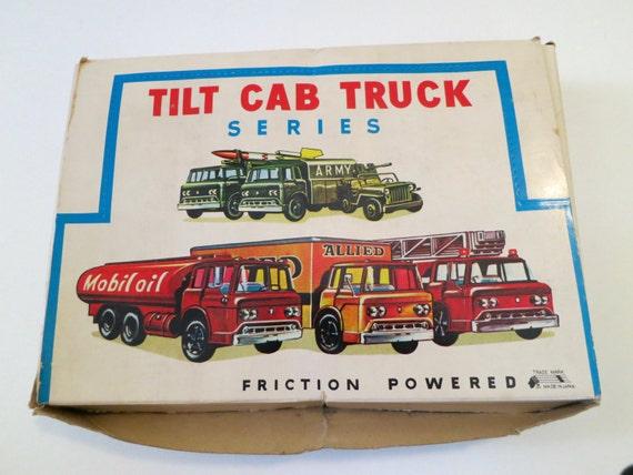 Six tin litho Japanese friction trucks in display box.