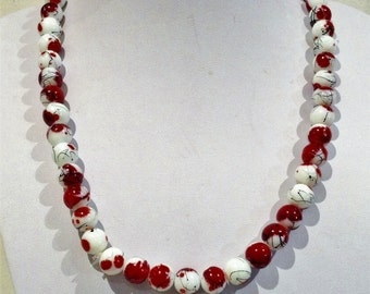 Necklace53cm Features High Quality Enamelled round Glass beads. White. Red splash patterns