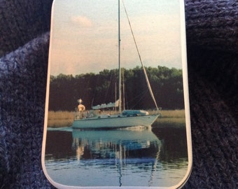 Decorative tin with picture of sailboat on the cover