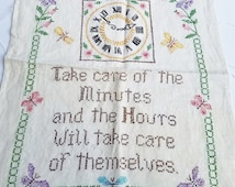 Completed Crossed Stitch Fabric Piece with Take Care of the Minutes Phrase