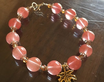 Coral pink beaded bracelet with gold leaf charm