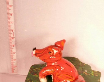 A cute fox washing his paw on a small green box, in the shape of a present.  Made from Fimo / Polymer clay