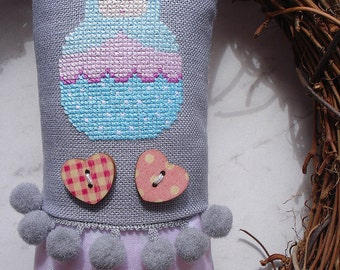 Cross stitch ornament with motif of matryoshka.