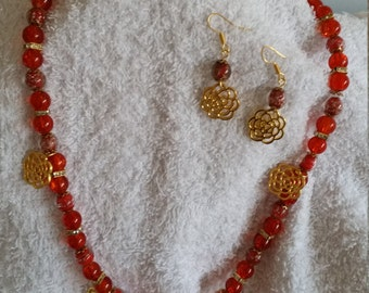 Gold floral pendant necklace with matching earrings.