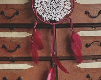 Crimson dream catcher made with leather and feathers.