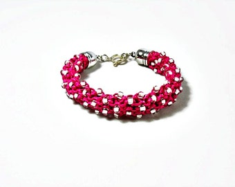 Knitted beaded bracelet with fuchsia color ribbon yarn and Toho beads