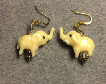 Opaque pale yellow lampwork elephant bead earrings adorned with light yellow Czech glass beads.