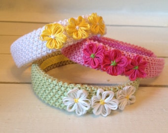 1 inch wide hard headband covered with textured hand-knitted cotton and trimmed with handmade daisies.